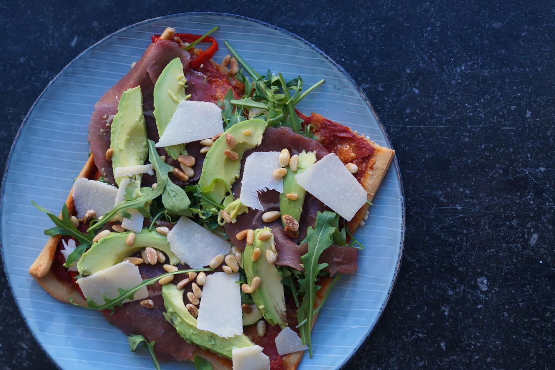 Pizza Med Bresaola, Rucola, Avocado, Friskhøvlet Parmesan Og Pinjekerner - Julie Bruun